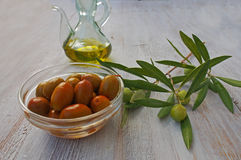 Extra-virgin olive oil bottle and green olivas Royalty Free Stock Photos