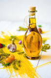 Extra virgin olive oil. A bottle of extra virgin olive oil and pasta with yellow cherry tomatoes and garlic Stock Image