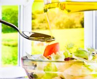 Extra virgin olive oil bottle pouring in the Italian fresh salad Royalty Free Stock Photography
