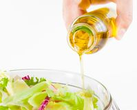 Extra virgin olive oil bottle pouring in the Italian fresh salad isolated Royalty Free Stock Images