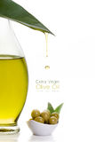 Extra Virgin Olive Oil. Close up extra olive oil on glass bottle with olive seeds on white bowl and a fresh green leaf with a droplet suspended midair over a Stock Photography