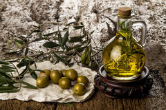 Extra virgin olive oil flavored. Extra-flavored olive oil with rosemary, on old wooden table Stock Image