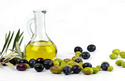 Extra virgin olive oil with fresh olives. Cold pressed, extra virgin olive oil in a decorative glass jar, from Spain, with a fresh crop of autumn picked black Royalty Free Stock Photography