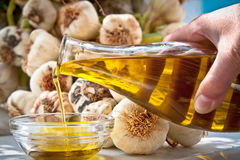 Extra-virgin olive oil and garlic. Hand pouring extra-virgin olive oil in a bwol with fresh garlic in the background Royalty Free Stock Images