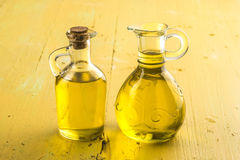 Extra virgin olive oil glass jars. Two virgin olive oil glass jars on yellow wooden table Stock Photo