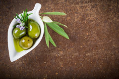Extra virgin olive oil and green olives Stock Photos
