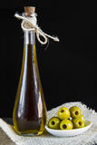 Extra virgin olive oil and pitted green olives Stock Images