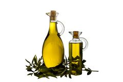 Extra Virgin olive oil in two glass rustic  bottles. And leaves  isolated over a white background stock images