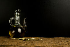 Extra virgin olive oil vintage cruet. Olive oil, extra virgin olive oil vintage cruet on old wooden table with dark blank space for message Royalty Free Stock Image