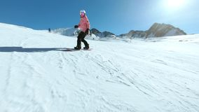 Young hipster female snowboarder on sunny slope. Extra wide shot of active lifestyle hipster young woman in pink cute ski jacket ride snowboard down empty smooth stock video footage