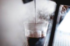 Extracción de un café express con la luz brillante fotos de archivo
