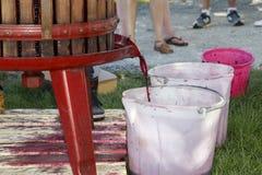 Extracción del jugo de uva con la prensa de vino manual vieja Fotografía de archivo