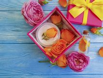 Extract, essence gift box cosmetic product bow composition cream beautiful fresh orange rose on a blue wooden background stock photo