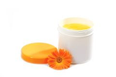 Extract of Marigold. Cream pot with marigold on white background royalty free stock images