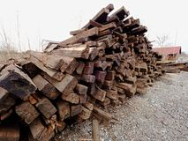 Extracted old wooden ties in stock. Old oiled used oak railway sleepers stored after reconstruction Stock Image