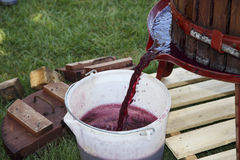 Extracting grape juice with old manual wine press. Red grape juice extraction for making red wine with an old manual wine press stock photos