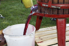 Extracting grape juice with old manual wine press. Red grape juice extraction for making red wine with an old manual wine press royalty free stock image