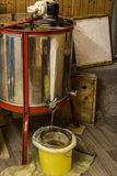 Extracting honey, honey flowing out of centrifuge into a sieve hanging in a bucket Royalty Free Stock Image