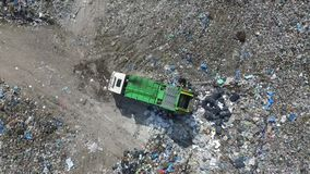 Extracting trash from garbage truck, aerial view. The garbage truck goes between the top of the garbage, aerial view, a green garbage truck goes between the stock video