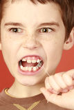 Extraction. Determination young boy, extraction milk tooth, lost healthy milk-tooth, young tough boy pulling a tooth out, piercing toothache Stock Photos