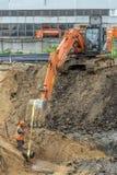 Extraction d'un tuyau à l'aide d'une excavatrice images libres de droits