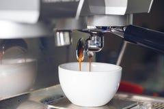 Extraction de café versant dans une tasse du café professionnel mA photos stock