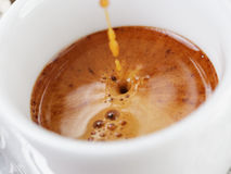 Extraction of espresso with rich crema in cup. Close up photo Stock Photo