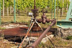Extraction of good quality oil. Oil well pumpjack on vineyard in Czech Republic. Southern Moravia Region. Royalty Free Stock Photography