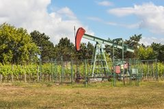 Extraction of good quality oil. Oil well pumpjack on vineyard in Czech Republic. Southern Moravia Region. Stock Images