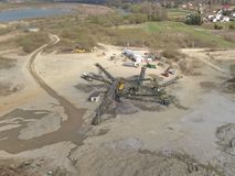Extraction, washing, sorting and distraction of river gravel. Mining industry. Technology of obtaining a stone. A bird`s eye view. Shooting with a quadrocopter royalty free stock image