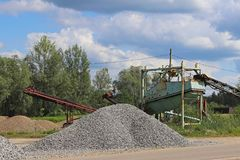 Extraction, washing, sorting and distraction of river gravel. Mining industry. Technology of obtaining a stone. A bird`s eye view. Shooting with a quadrocopter stock photos