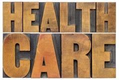 Extracto de la palabra de la atención sanitaria en el tipo de madera foto de archivo