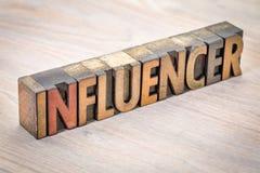 Extracto de la palabra de Influencer en el tipo de madera foto de archivo