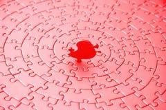 Extracto de rompecabezas en rojo y rosado con el pedazo pasado de pie Foto de archivo libre de regalías