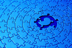 Extracto de un rompecabezas azul con el espacio y uno de los pedazos que falta en el centro Imagen de archivo libre de regalías