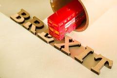 Extracto en letras del vintage, modelo del juguete del autobús del autobús de dos pisos del fondo, túnel de la palabra de Brexit Imagen de archivo libre de regalías