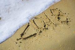 Extracto 2018 en un fondo de la arena de la playa Imagen de archivo