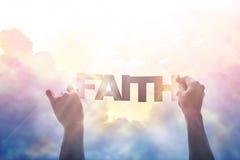 Extracto, mano que lleva a cabo una fe de la palabra en el cielo colorido en la naturaleza Imagen de archivo