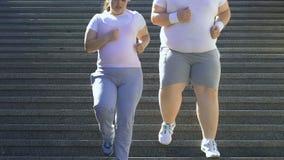 Extragewichtspaare, die unten, draußen trainierend, brennende Kalorien laufen stock footage