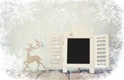 Extrahieren Sie gefiltertes Foto des dekorativen Tafelrahmens und hölzerne Rotwild über Holztisch bereiten Sie für Text oder Mode Stockfoto