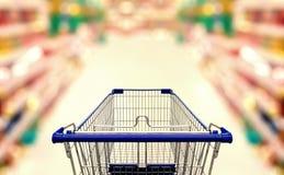 Extrahieren Sie unscharfes Foto des Supermarktes mit leerem Warenkorb Lizenzfreie Stockfotos