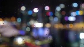 Extrahieren Sie unscharfes Licht mit Bürogebäude und Reflexionsnachtansicht über Singapur mit regnerischen Tropfen auf dem Fenste stock video footage