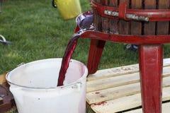 Extrahierung des Traubensafts mit alter manueller Weinpresse Lizenzfreies Stockbild