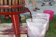 Extrahierung des Traubensafts mit alter manueller Weinpresse Stockfotografie