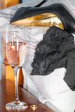 Extramarital affair. Drunken sex with a married woman. Black stockings and leather stiletto heel shoe on a bed next to pink champagne alcohol and a wedding royalty free stock photography