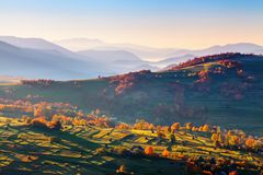 Extraordinary autumn landscape. Green fields with haystacks. Trees covered with orange and crimson leaves. Mountain landscapes. Nice rays of the sun. Location Royalty Free Stock Images