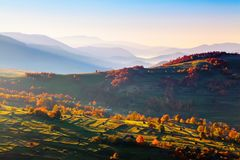 Extraordinary autumn scenery. Green fields with haystacks. Trees covered with orange and crimson leaves. Mountain landscapes. Nice rays of the sun. Location stock images