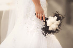 Extraordinary designer wedding bouquet from feathers in black and white colors. In bride hands Royalty Free Stock Photos
