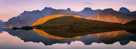 Extraordinary panorama of Lofoten Islands, Norway. Extraordinary summer sunset panorama of Lofoten Islands, Norway, with mountains, fjord, and purple reflections Stock Photo