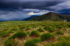 Extraordinary stormy sky with rain clouds is spanned over the high mountain. Stock Images